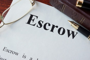 Paper with word Escrow and glasses on a table.