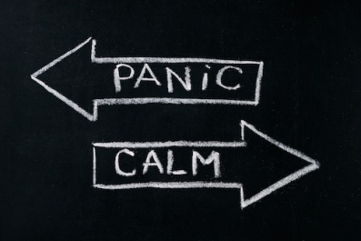 Panic or calm stop panicking stay easy and relaxed keep calming down handwritten on blackboard.