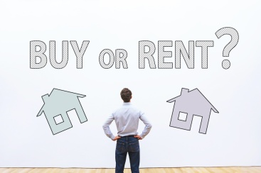 Man looks at sign to choose buy or rent.